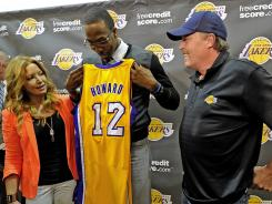 Lakers center Dwight Howard stands between Jeanie Buss and Jim Buss as he holds his jersey during a news conference held to introduce the three-time defensive player of the year, who was acquired in a four-team trade from the Magic.