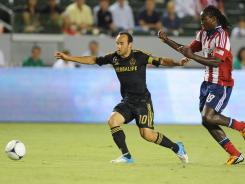 Galaxy midfielder Landon Donovan (10) moves the ball defended by Chivas USA midfielder Shalrie Joseph (18) during the first half at the Home Depot Center.