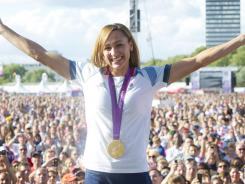 Britain's Jessica Ennis, hold her arms aloft after winning the gold medal in the heptathlon during the London Olympics, where she greeted fans on stage at the BT London Live concert at Hyde Park.