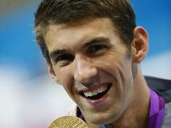 Aug 3, 2012; London, United Kingdom; USA swimmer Michael Phelps celebrates with his gold medal after winning the men's 100m butterfly final during the London 2012 Olympic Games at the Aquatics Centre.