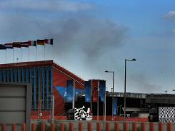 Smoke rises from a fire at a recycling center on Chequers Lane in Dagenham, east London, behind the Olympic Park's BMX track on Sunday.