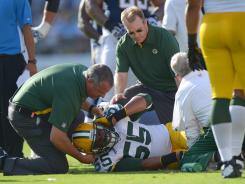 Green Bay Packers linebacker Desmond Bishop is tended to by members of the Packers' training staff after suffering an injury against the San Diego Chargers on Aug. 9, 2012.