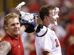 The Reds' Jay Bruce, right, gets a shaving cream pie in the face from starter Mat Latos after hitting a game-winning, three-run homer in the ninth inning.