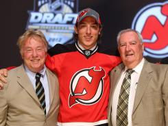 Stefan Matteau (center), 29th overall pick by the New Jersey Devils, poses with Devils representatives on stage during the 2012 NHL Draft.