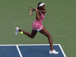 Venus Williams follows through on a backhand during her three-set victory Tuesday against Maria Kirilenko of Russia at the Western & Southern Open in Mason, Ohio.