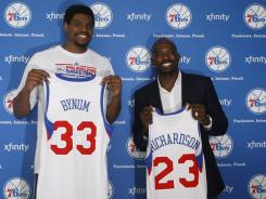 Philadelphia 76ers players, Andrew Bynum, left, and Jason Richardson, pose with their new jerseys after being introduced at a news conference in Philadelphia.
