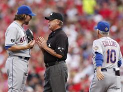Umpire and crew chief Jim Joyce talks with Mets starter R.A. Dickey, left, as manager Terry Collins walks to the mound during the second inning.