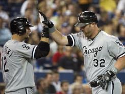 White Sox first baseman Adam Dunn, right, celebrates with teammate A.J.Pierzynski after hitting a three-run home run against the Blue Jays during the seventh inning.