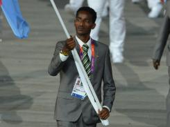 Eritrea flagbearer Weynay Ghebresilasie, leading his delegation during the opening ceremony, intends to seek political asylum in Britain.