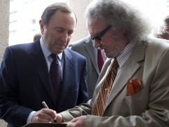 NHL Commissioner Gary Bettman signs an autograph as he arrives for collective bargaining talks in Toronto.