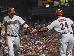The Diamondbacks' Paul Goldschmidt, left, is congratulated by Chris Young after hitting a solo home run to tie the game in the ninth inning. Young followed up with solo shot of his own on the next pitch.
