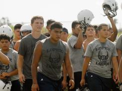 Lopez (Brownsville, Texas) players head for a water break during practice Monday. Texas is one of several states that banned consecutive two-a-day practices this season.