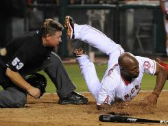 The Angels' Torii Hunter collides with umpire Greg Gibson while sliding into home during the fifth inning.