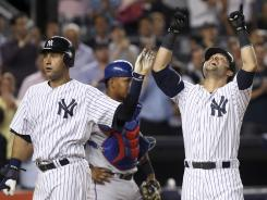 The Yankees' Nick Swisher, right, celebrates his two-run homer with Derek Jeter during the seventh inning. Swisher also homered in the first inning and Jeter homered in the fifth.