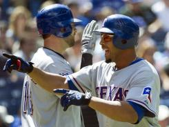 Texas Rangers' Nelson Cruz, right, celebrates after hitting a two-run home run against the Toronto Blue Jays during fifth inning baseball action in Toronto on Saturday.