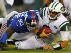 Giants defensive end Jason Pierre-Paul (90) sacks Jets quarterback Mark Sanchez (6) during the first half of Saturday night's preseason game.