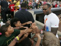 NBA star LeBron James greets third and fourth graders from the Akron Public Schools during an appearance at a minor league baseball game Sunday in his native Akron, Ohio.