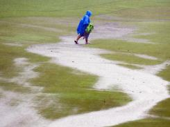 A spectator crosses the flooded fifth fairway after play was suspended during the final round of the Wyndham Championship on Sunday in Greensboro, N.C.