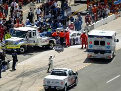 Safety crews tend to Mark Martin and his No. 55 Toyota after he crashed into a pit road barrier during Sunday's Pure Michigan 400.
