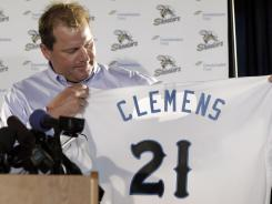 Roger Clemens holds up his new jersey during a Tuesday news conference officially announcing his signing with the Sugar Land Skeeters.