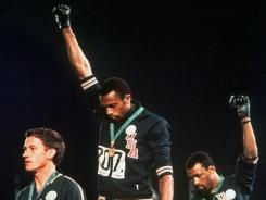 Extending gloved hands skyward in racial protest, U.S. athletes Tommie Smith, center, and John Carlos, stare downward during the playing of the Star Spangled Banner after Smith received the gold and Carlos the bronze for the 200 meter run at the 1968 Olympics in Mexico City. Australian silver medalist Peter Norman is at left.