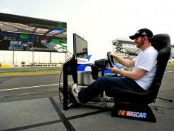 Shown in May 2011 at Charlotte Motor Speedway, Dale Earnhardt Jr. plays a video game that is displayed on a giant HDTV at the 1.5-mile track.