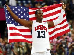 Chris Paul hoists the U.S. flag after a gold medal victory Aug. 12 against Spain at the London Olympics.