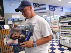 Perry Rearick of Bellefonte, Pa., looks at a copy of Paterno at the Student Book Store in State College, Pa., on Tuesday, the first day it was available in stores.
