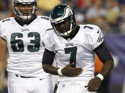 Eagles QB Michael Vick holds his ribs after a punishing shot from the Patriots on Monday night.