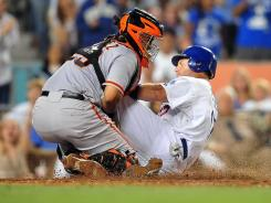 Giants catcher Hector Sanchez, left, blocks the plate and tags the Dodgers' A.J. Ellis in the sixth inning, preserving a 4-1 lead.