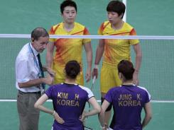 An unidentified official talks to women's doubles pair of South Korea's Jung Kyung-eun (foreground right) Kim Ha-na (foreground left), and China's Yu Yang (background left), Wang Xiaoli (background right) after they allegedly deliberately made mistakes to lose the match at the London Olympics on July 31.
