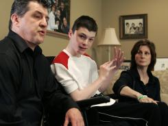 Steven Domalewski, center, sits with his parents Joseph and Nancy Domalewski during an interview at their home in Wayne, N.J. Domalewski, left brain-damaged after being struck by a line drive while he was playing in a youth baseball game, will receive $14.5 million to settle his lawsuit against the bat manufacturer, Little League Baseball and a sporting goods chain. The settlement of was announced in state Superior Court on Wednesday.