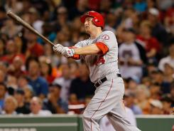 The Angels' Mark Trumbo hits his 30th home run of the season off Boston's Aaron Cook during the fifth inning at Fenway Park.