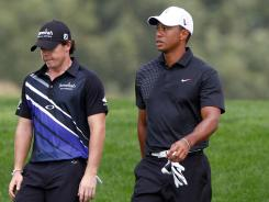 Rory McIlroy and Tiger Woods, playing with Zach Johnson, walk down the 18th fairway Thursday during Round 1 of The Barclays at Bethpage State Park.