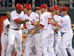 The Phillies' John Mayberry Jr., front left, is mobbed by teammates after hitting a game-winning RBI single in the 11th inning to beat the Reds 4-3.