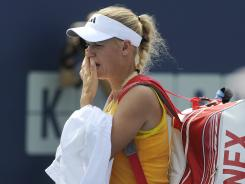 Caroline Wozniacki of Denmark leaves the court after retiring from her semifinal match after losing the first set 7-5 to Maria Kirilenko of Russia at the New Haven Open.