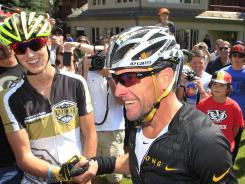 Lance Armstrong, right, talks to news reporters after his second-place finish in the Power of Four mountain bicycle race at the base of Aspen Mountain in Aspen, Colo., on Saturday. The race was won by 16-year-old Keegan Swirbul, left.