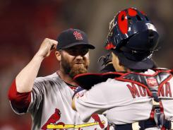 Cardinals reliever Jason Motte celebrates with catcher Yadier Molina after the win.