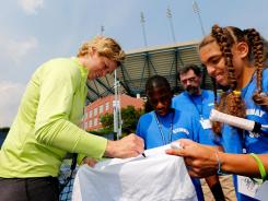 Kim Clijsters of Belgium signs her autograph for fans during a clinic Saturday before the start of the 2012 U.S. Open. Clijsters, a three-time champ, will retire after the Open.