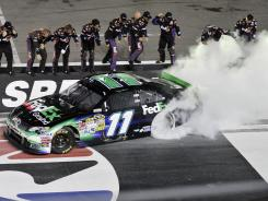 Denny Hamlin celebrates with his pit crew after winning the Irwin Tools Night Race.