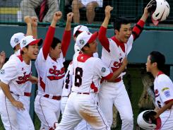 Tokyo's Noriatsu Osaka, second from right, celebrates with teammates after hitting a walk-off, two-run home run against Goodlettsville, Tenn., in the fifth inning of the Little League World Series. Tokyo won 12-2 in five innings.