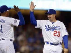 Adrian Gonzalez is congratulated by new teammate Ronald Belisario after the Dodgers' win Saturday.