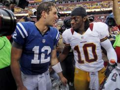 Indianapolis Colts quarterback Andrew Luck winks at Washington Redskins quarterback Robert Griffin III after an NFL preseason football game Saturday, Aug. 25, 2012, in Landover, Md.