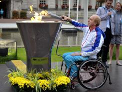 Torchbearer Simon Richardson lights the Paralympics Cauldron outside City Hall in Cardiff, Wales on Monday. The 2012 Summer Paralympic Games will be held from Aug. 29 to Sept. 9.