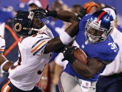 Loaded for Bear: Giants running back David Wilson, right, trying to avoid a stiff-arm by Charles Tillman during Friday's game, is playing well enough that he could take carries away from injured Ahmad Bradshaw.