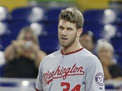 Nationals outfielder Bryce Harper looks on Wednesday as first base coach Trent Jewett argues with umpire C.B. Bucknor, who ejected Harper for slamming his helmet.