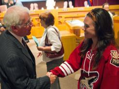 Prospective Coyotes owner Greg Jamison shakes hands with 17-year-old fan Laura Truswell during a break at a Glendale City Council meeting.