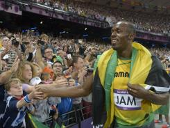 Usain Bolt celebrates with fans after winning the gold in the men's 4x100 relay final during the London Olympics on Aug. 11.