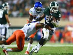 Michigan State running back Le'Veon Bell runs over Boise State cornerback Jamar Taylor in the fourth quarter at Friday night.