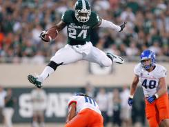 Michigan State's Le'Veon Bell hurdles the attempted tackle of Boise State's Jeremy Ioane on Friday night.